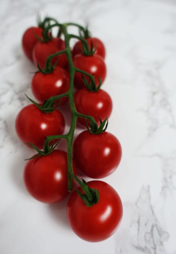 Glänzende rote Cherrytomaten mit Stiel sind Zutaten für den Spinat-Zitronen-Risotto