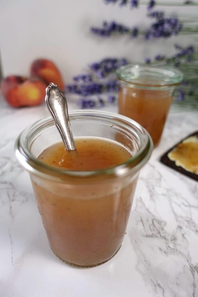 In einem Weckglas ist die Pfirsichmarmelade mit Lavendel angerichtet.