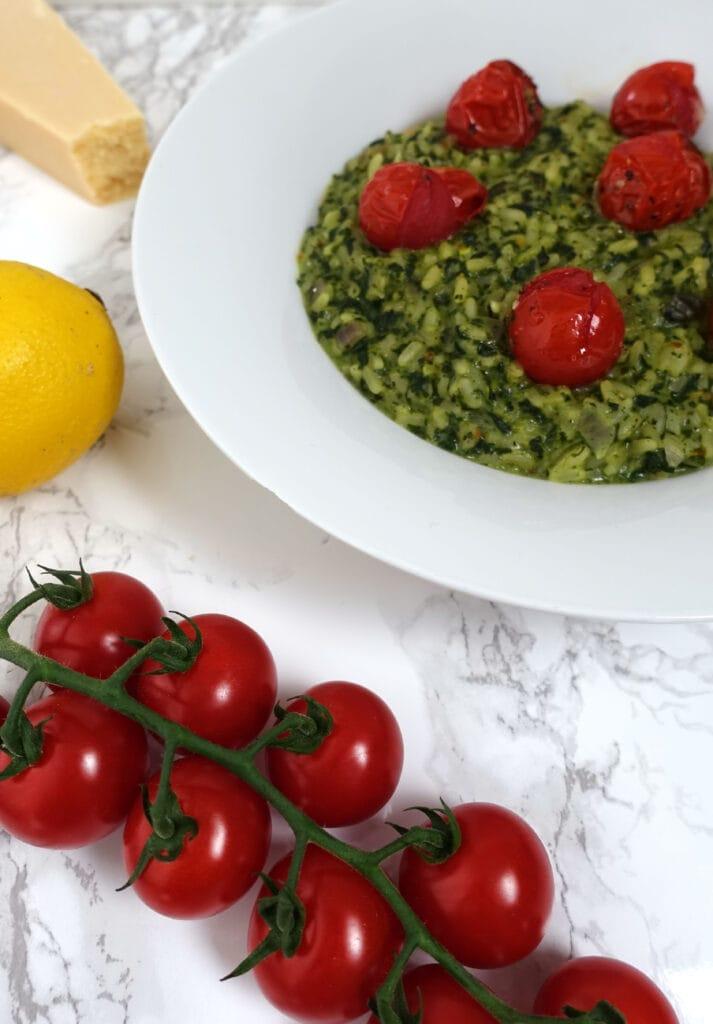 grüner Spinatrisotto mit roten Ofentomaten in einem weissen Teller Spinat-Zitronen-Risotto