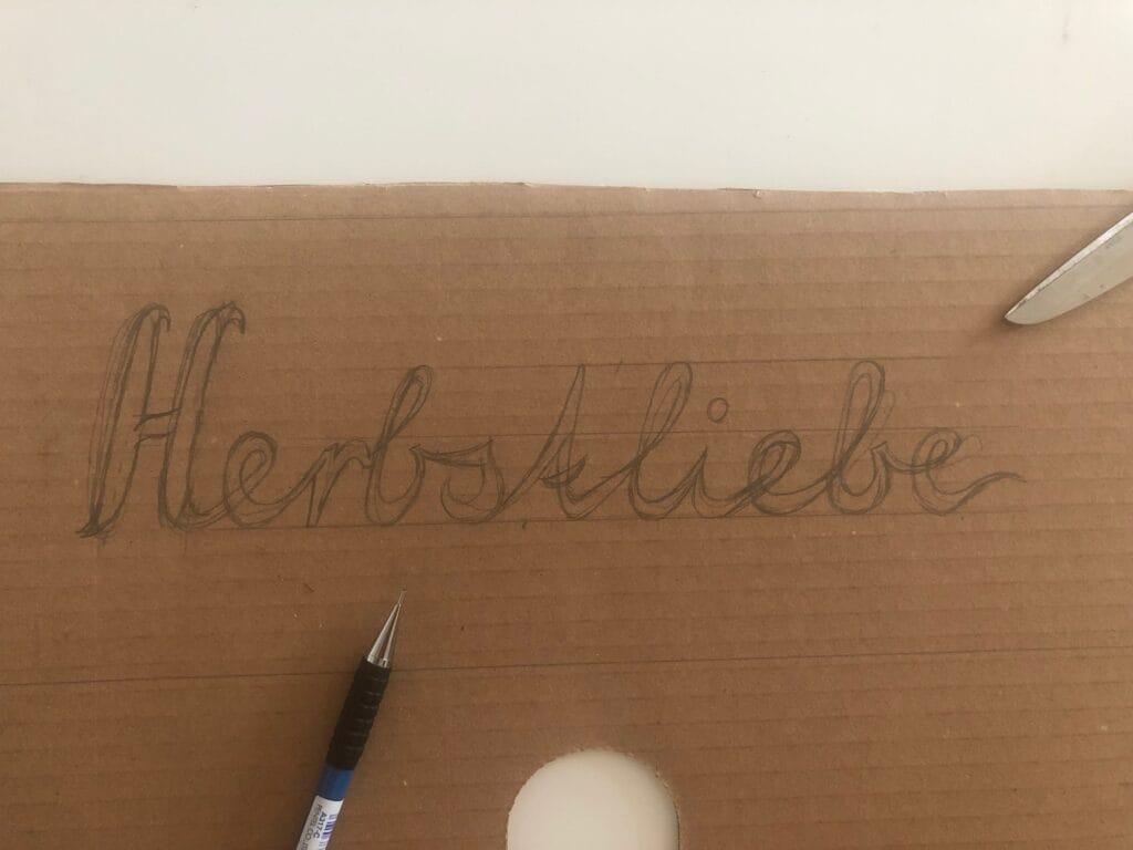 Mit Bleistift Schriftzug Herbstliebe vorzeichnen.