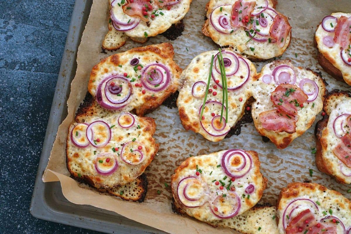 Flammkuchen Brotscheiben mit Zwiebeln, Speck und rosa Pfeffer