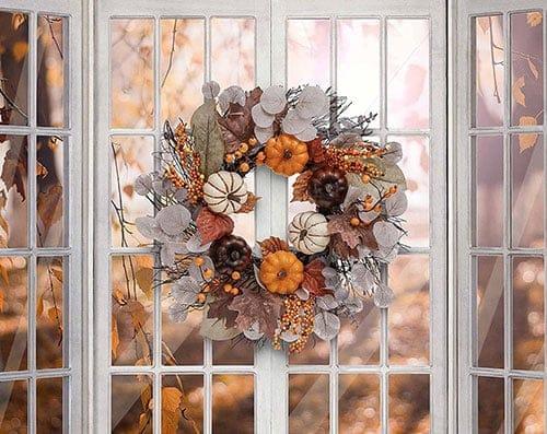 Ein Kranz zum Aufhängen aus herbstlichen Materialien wie Kürbissen und Blättern