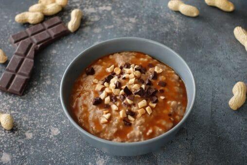 Snickers Porridge mit Haferflocken, Milch, Schokolade, Erdnüssen, Erdnussbutter, Kakaopulver und Karamellsauce