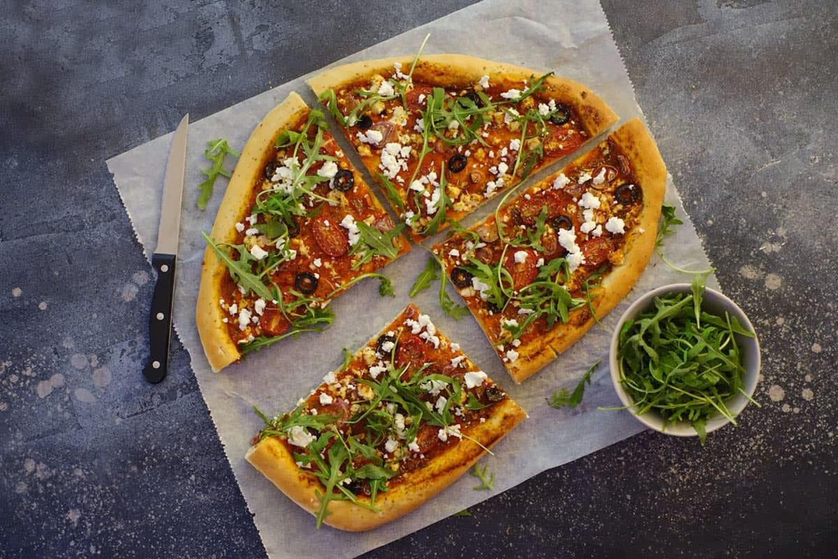 Pizza mit Ajvar, Rucola, Oliven, Feta Käse, Cherrytomaten und Gewürzen